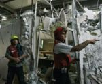 Tim pemadam kebakaran sedang memeriksa bangunan perbelanjaan yang hancur terkena roket Hamas di kota Askhelon, Israel.
